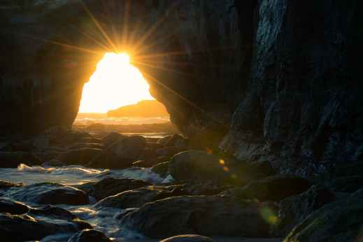 cave near body of water at sunset